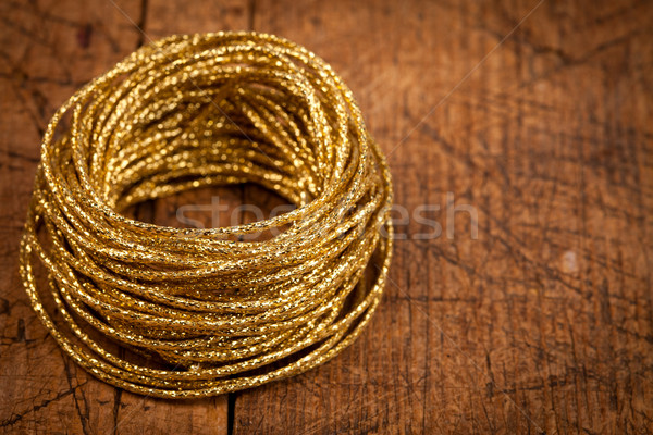Golden rope on wooden table Stock photo © kalozzolak