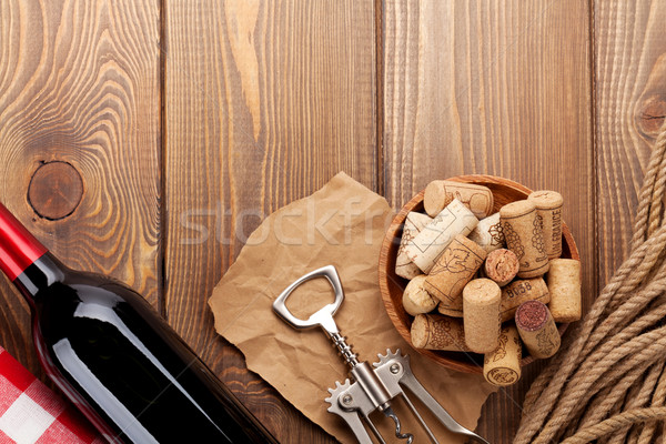 Red wine bottle, bowl with corks and corkscrew. View from above Stock photo © karandaev