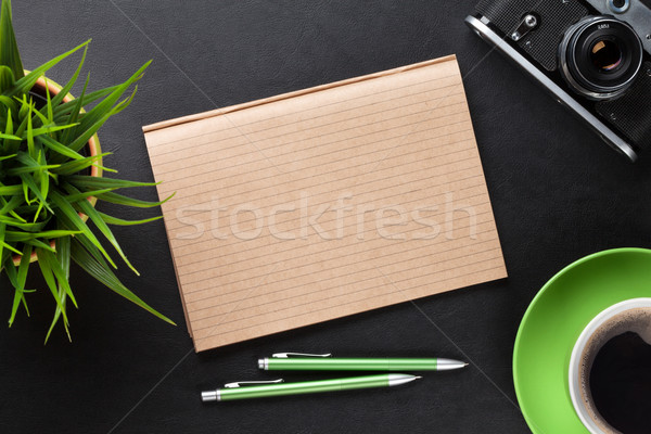 Stock photo: Desk with camera, supplies, coffee cup and flower