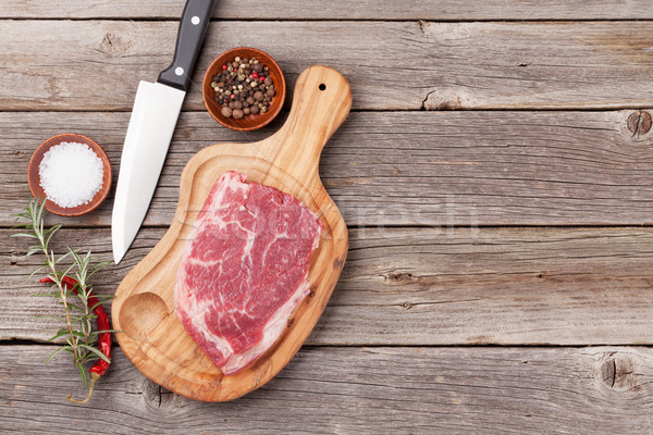 Raw beef steak and spices on wooden table Stock photo © karandaev