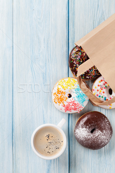 Colorful donuts in paper bag and coffee cup Stock photo © karandaev
