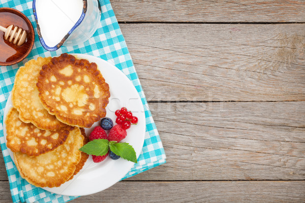 Pancakes with raspberry, blueberry, milk and honey syrup Stock photo © karandaev