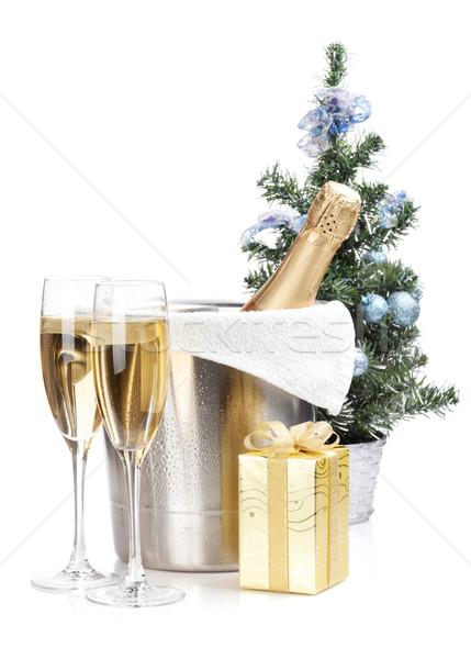 Champagne bottle in ice bucket, two glasses and christmas gift Stock photo © karandaev