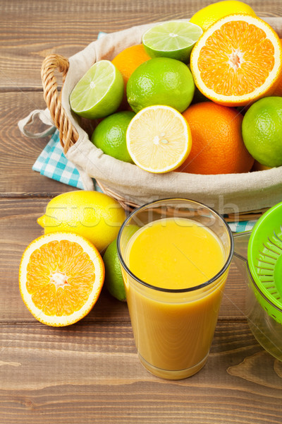 Citrus fruits in basket and glass of juice. Oranges, limes and l Stock photo © karandaev
