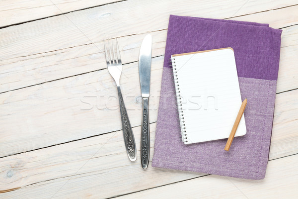 Notepad over kitchen towel and silverware on wooden table Stock photo © karandaev