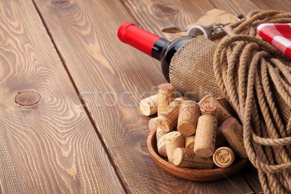 Red wine bottle, corks and corkscrew over wooden table backgroun Stock photo © karandaev