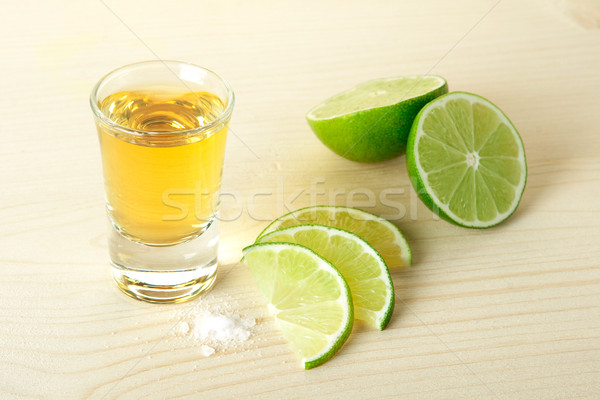Oro tequila cal rebanadas sal mesa de madera Foto stock © karandaev