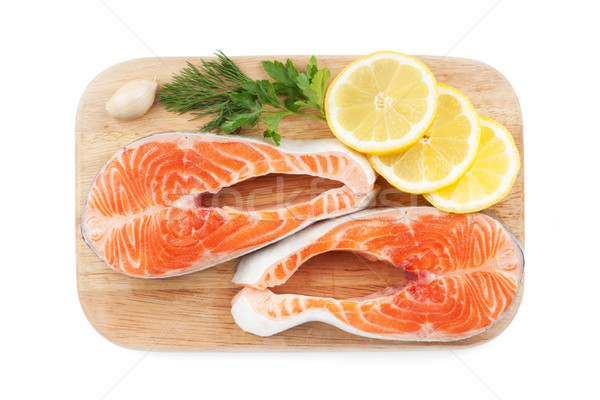 Salmon steaks with herbs and lemon slices on cutting board Stock photo © karandaev