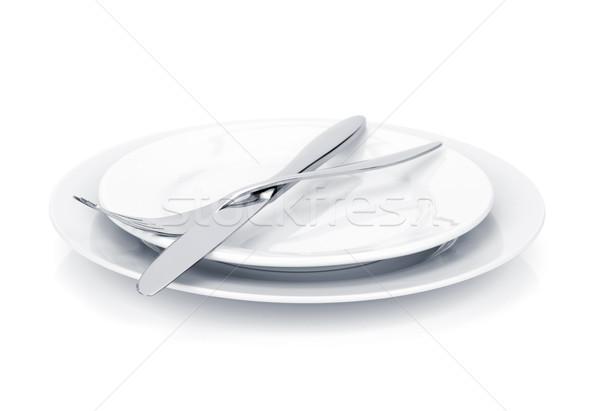 Silverware or flatware set of fork and knife over plates Stock photo © karandaev