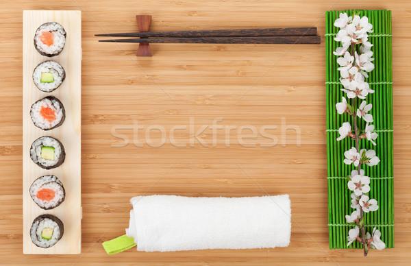 Sushi set with fresh sakura branch over bamboo table Stock photo © karandaev