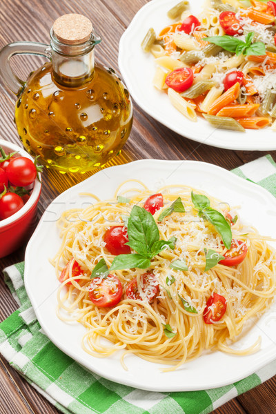 Spaghetti and penne pasta with tomatoes and parsley Stock photo © karandaev