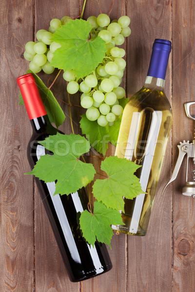 Köteg szőlő bor üvegek dugóhúzó fa asztal Stock fotó © karandaev