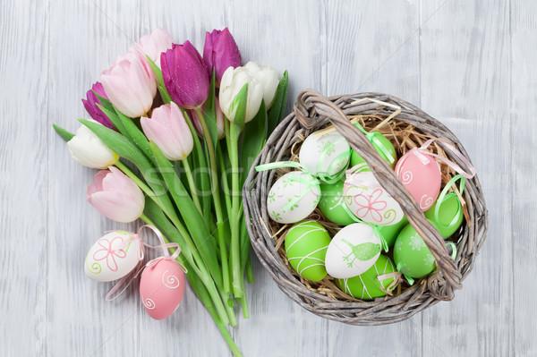 Easter eggs in basket and tulips Stock photo © karandaev