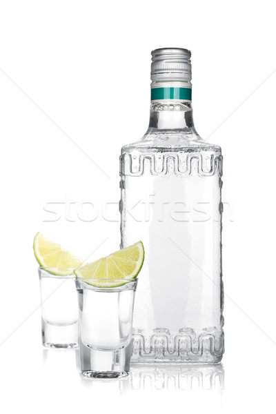 Bottle of silver tequila and two shots with lime slice Stock photo © karandaev