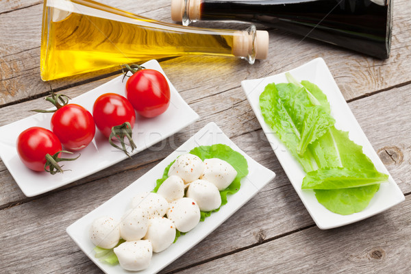 Stock photo: Tomatoes, mozzarella and green salad leaves with condiments
