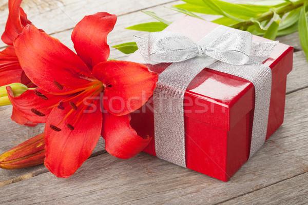 Rosso giglio fiore scatola regalo tavolo in legno fiori Foto d'archivio © karandaev