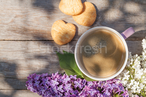 Stock photo: Coffee cup and colorful lilac flowers on garden table