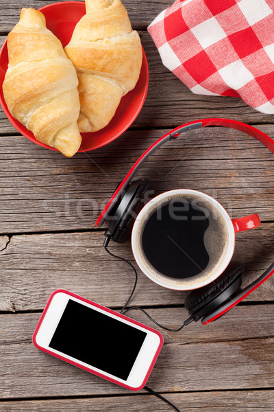 świeże rogaliki kawy smartphone słuchawki drewniany stół Zdjęcia stock © karandaev