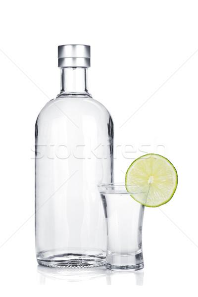 Bottle of vodka and shot glass with lime slice Stock photo © karandaev