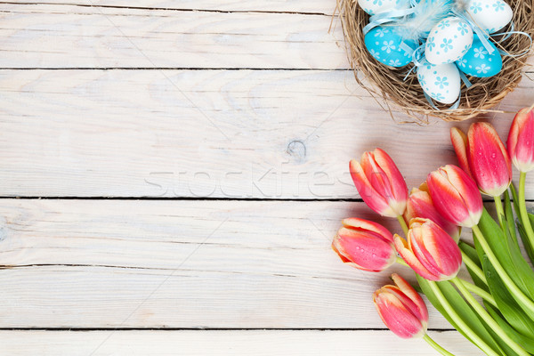 Colorful tulips and easter eggs in nest on wooden table Stock photo © karandaev