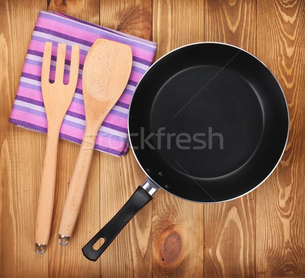 Frying pan and kitchen utensils on wooden table Stock photo © karandaev