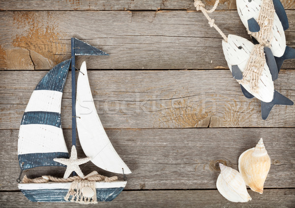 Toy sailboat and fish with seashells on a wooden background Stock photo © karandaev
