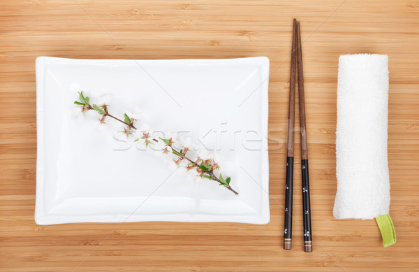 Empty plate, chopsticks and sakura branch Stock photo © karandaev