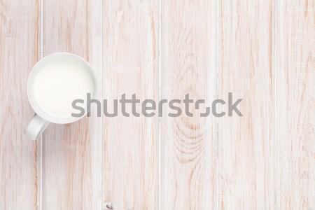Cup of milk on white wooden table Stock photo © karandaev