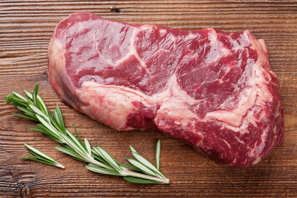 Raw ribeye beef steak cooking with rosemary Stock photo © karandaev