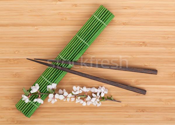 Chopsticks and sakura branch over mat Stock photo © karandaev