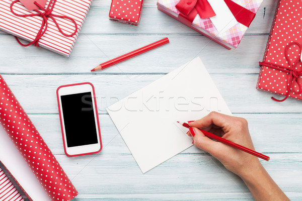 Female writing greeting card and wrapping christmas gifts Stock photo © karandaev