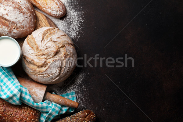 Stock photo: Various crusty bread and buns and milk