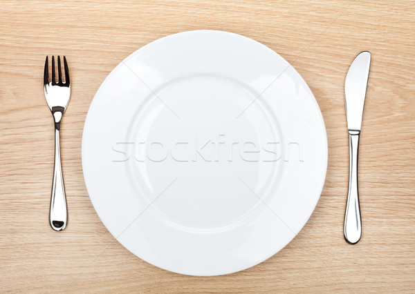 Stock photo: Empty white plate with silverware on wooden table