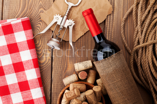Stock photo: Red wine bottle, bowl with corks and corkscrew. View from above