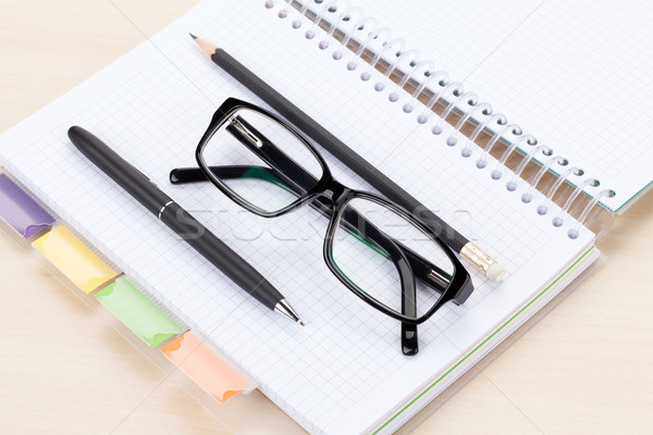 Office table with glasses over notepad, pen and pencil Stock photo © karandaev