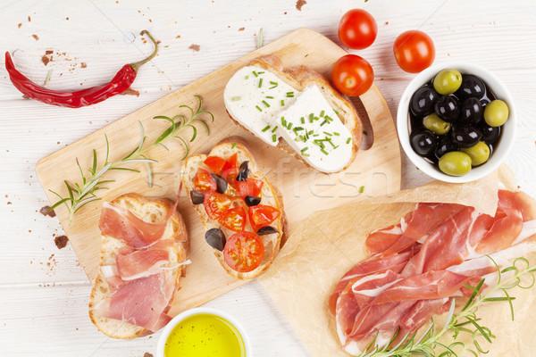 Bruschetta with cheese, tomatoes and prosciutto Stock photo © karandaev