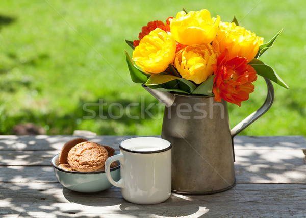 Colorful tulips in watering can, cookies and milk Stock photo © karandaev