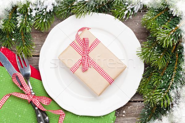 Christmas gift box over dinner plate, silverware, fir tree Stock photo © karandaev