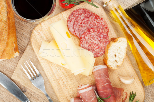 Red wine with cheese, prosciutto, bread, vegetables and spices Stock photo © karandaev