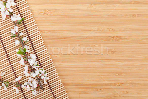 Stock photo: Sakura branch over bamboo mat