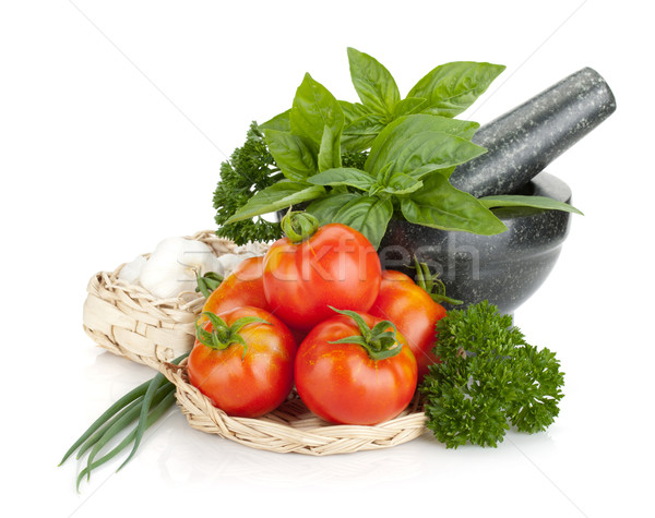 Ripe tomatoes and fresh herbs and spices in mortar Stock photo © karandaev