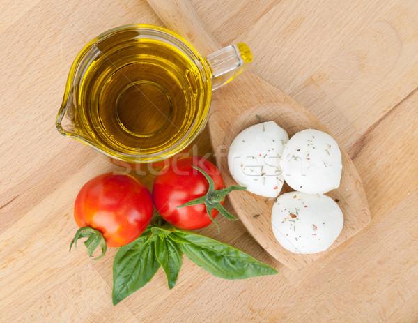 Mozzarella aceite de oliva tomates albahaca mesa de madera alimentos Foto stock © karandaev