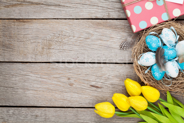 Easter background with blue and white eggs in nest, yellow tulip Stock photo © karandaev