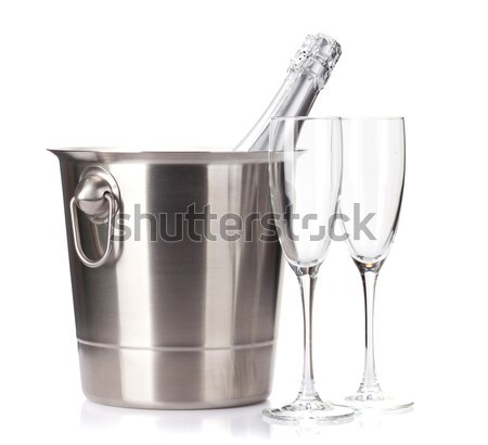 Champagne bottle in ice bucket and two empty glasses Stock photo © karandaev