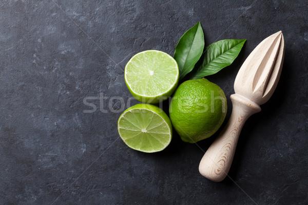 Limes and juicer Stock photo © karandaev