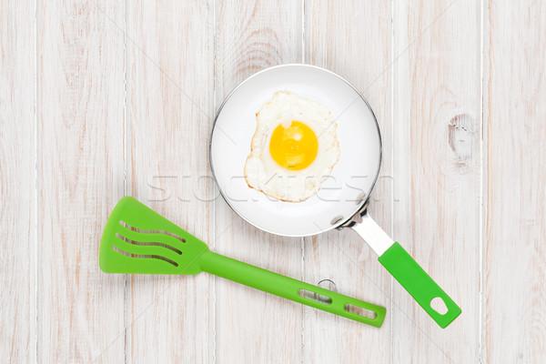 Fried egg in a frying pan Stock photo © karandaev