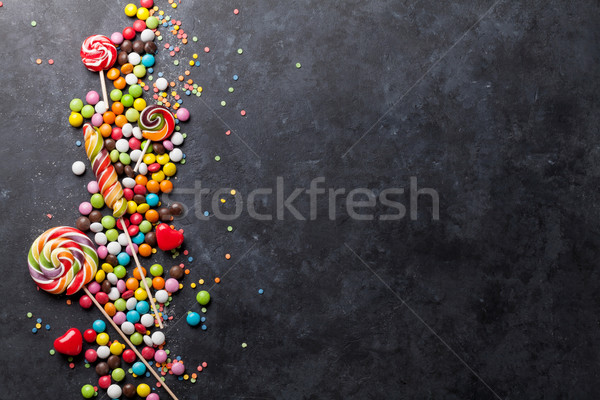Colorful candies and lollipops over stone Stock photo © karandaev