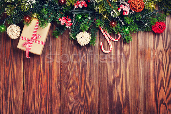 Fir tree branch with christmas lights, gift box and candy canes Stock photo © karandaev