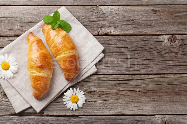 Croissants manzanilla flores mesa de madera superior vista Foto stock © karandaev