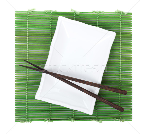 Chopsticks and plate over bamboo mat Stock photo © karandaev